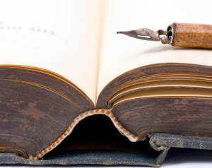 An old book that is open with a calligraphy pen on top.